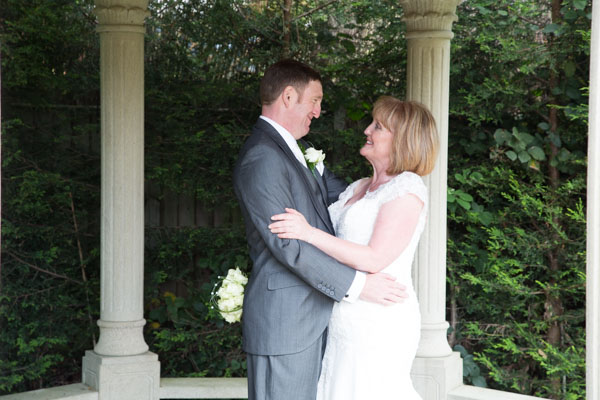 Bride and Groom looking at each other in Stone gazebo at Holiday Inn Barnsleys Secret Garden