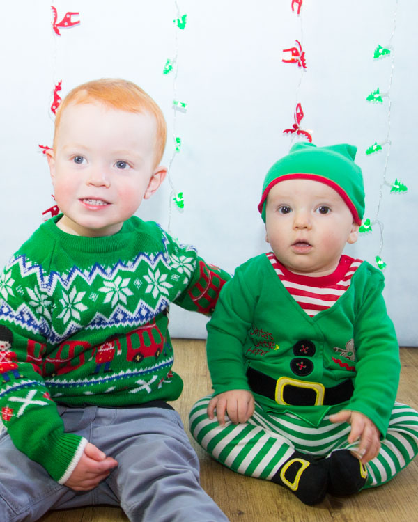 Brothers in elf outfits in front of a Christmas backdrop