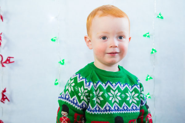 Boy with ginger hair looking at the vcamera in a green christmas jumper Christmas photo shoots