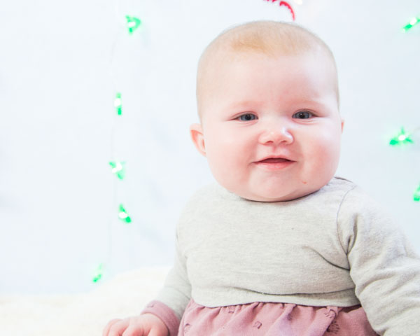 Baby girl smiling at the camera in front of a christmas backdrop Christmas photo shoots