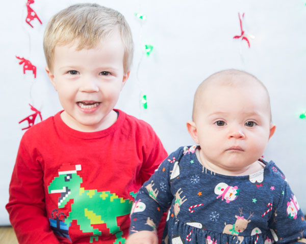 Brother and sister looking at the camera in front of a christmas backdrop