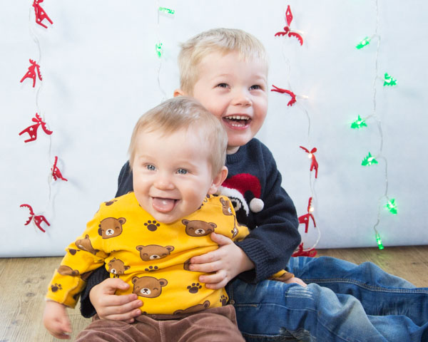 Two brothers laughing during a christmas photo shoots