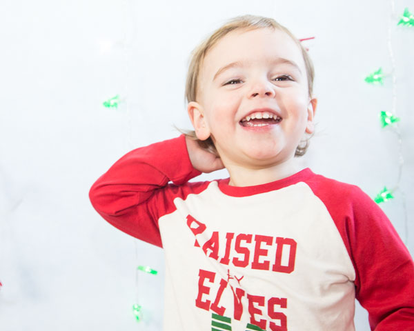 Toddler posing and laughing with Christmas tshirt Christmas photo shoots