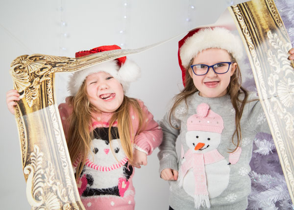 Two girls playing with a photo frame during a Christmas photo shoot