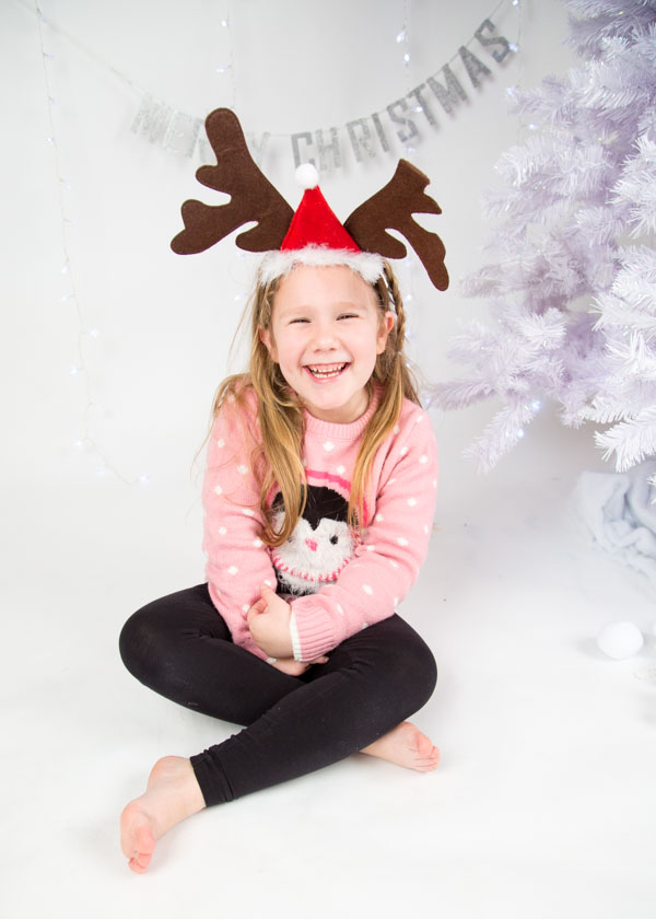Girl with christmas antlers laughing next to the christmas tree in her christmas jumper