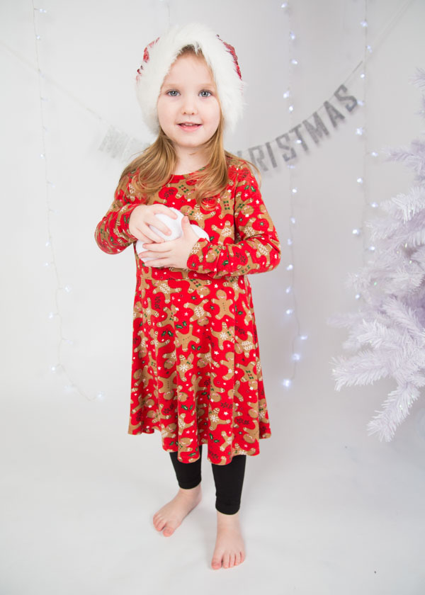 Girl in a christmas dress and santa holding a snowball during a christmas photo shoot
