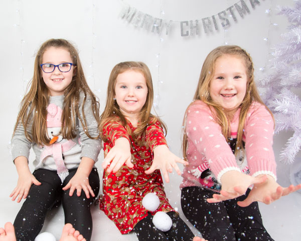 Three girls throwing snow during a christmas photo shoot