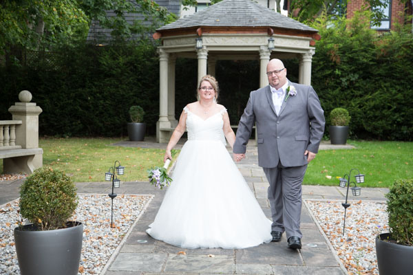 Bride and Groom walking down a path in Holiday Inn Barnsley Secret Garden Wedding