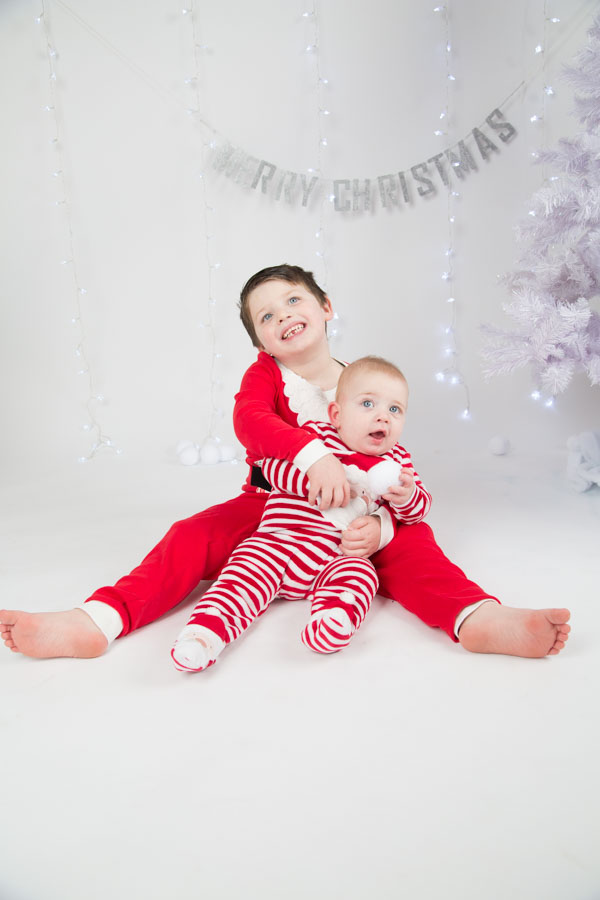 Two brothers cuddling during a christmas photo shoot
