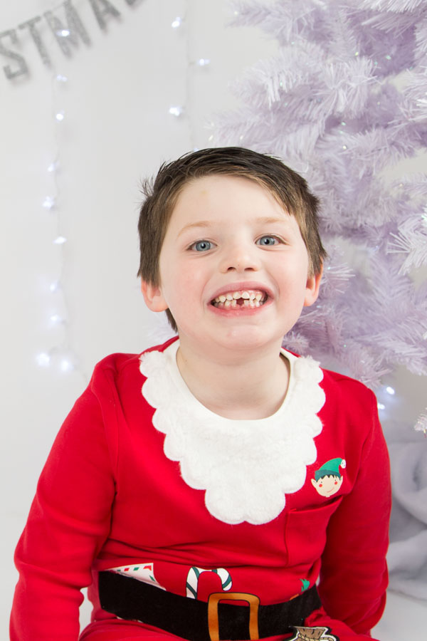 Boy in santa outfit looking at the camera and smiling Christmas photo shoots