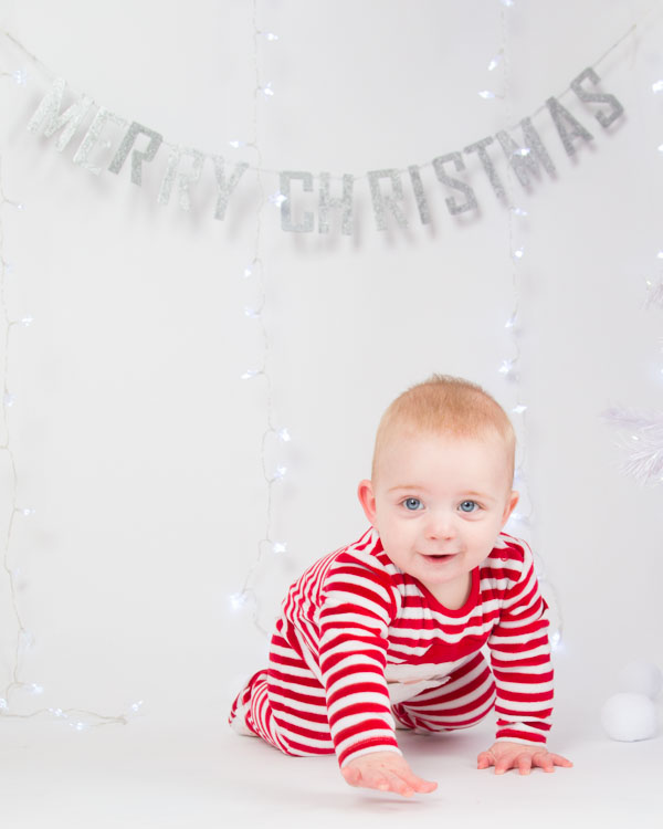 Baby crawling to the camera with merry christmas sign in the background Christmas photo shoots