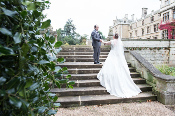 Groom helping Bride up stone steps at Thoresby Courtyard wedding