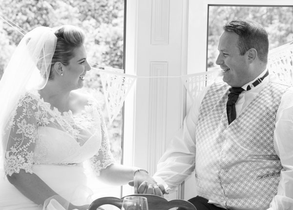 Bride and Groom looking at each other and smiling while sitting in the window of Quintessential catering Barnsley