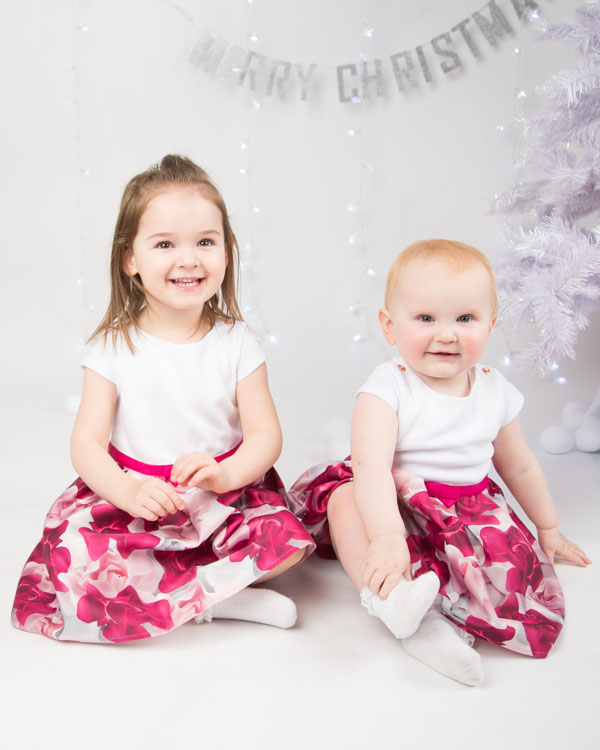 Two girls in matching dresses during a christmas shoot