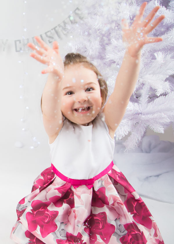 Girl throwing glitter in front of a christmas tree Christmas photo shoots