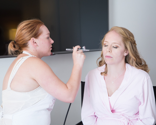 Makeup artist using airbrush foundation on bridesmaid wearing pink robe