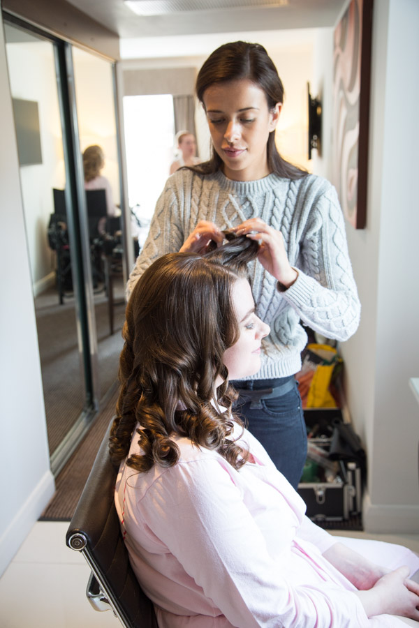 Hairdresser doing a bridesmaids hair with the make up artist in the background with a bridesmaid