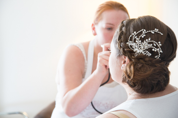Bride with makeup artist on the morning in the wedding showing off her diamante hair piece
