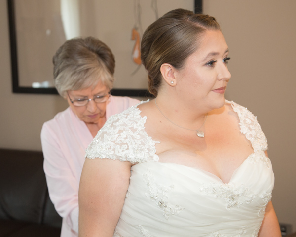 Mother of the bride fastening the wedding dress