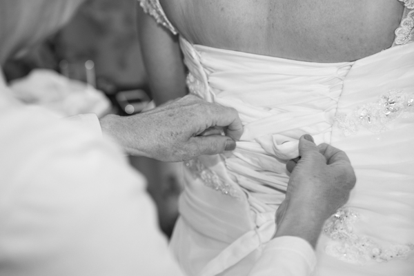 Close up of hands fastening the wedding dress