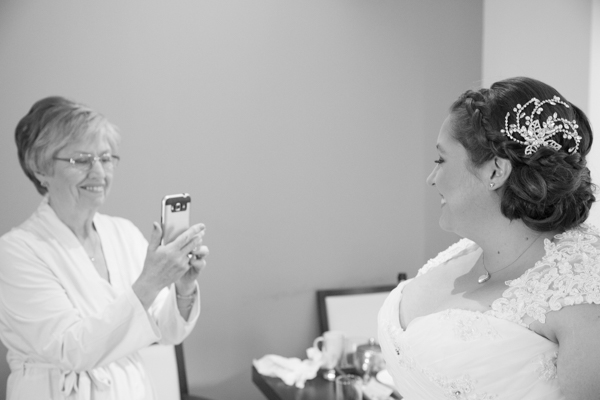 Mother of the bride photographing the bride and smiling