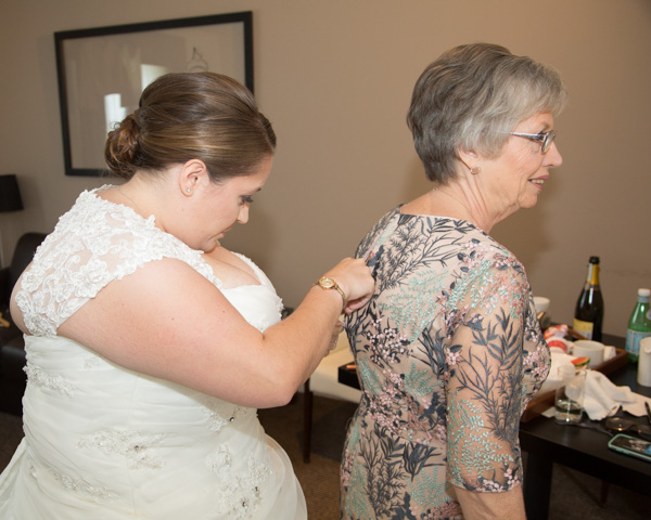 Bride fastening mothe rof the brides dress at Doubletree Hotel Chester