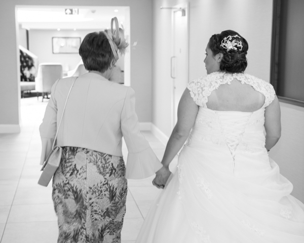 Bride and Mother of the bride holding hands and walking through the hotel