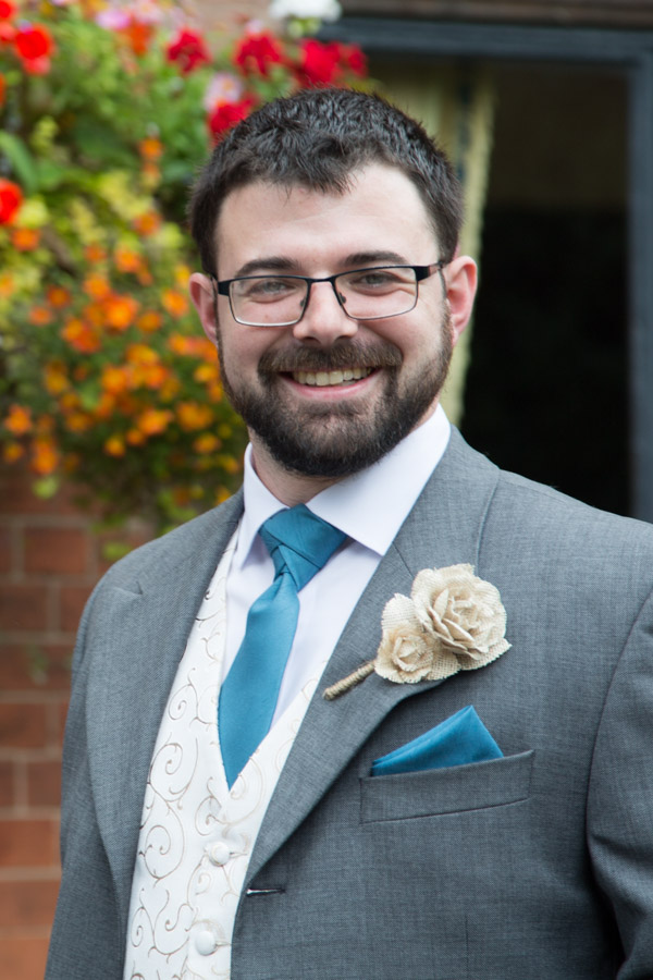 Groom in blue suit with paper buttonhole