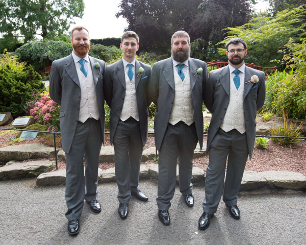 Groomsmen posing in front of walled garden at Chester Zoo wedding