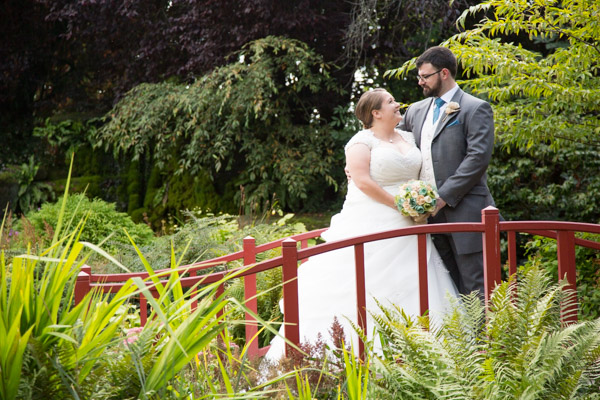 Bride and groom standing on red bridge in a garden at CHester zoo on their wedding day