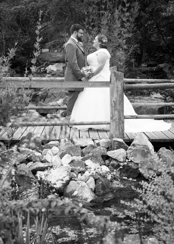 Bride and groom looking at each other on a bridge in gardens at Chester Zoo wedding