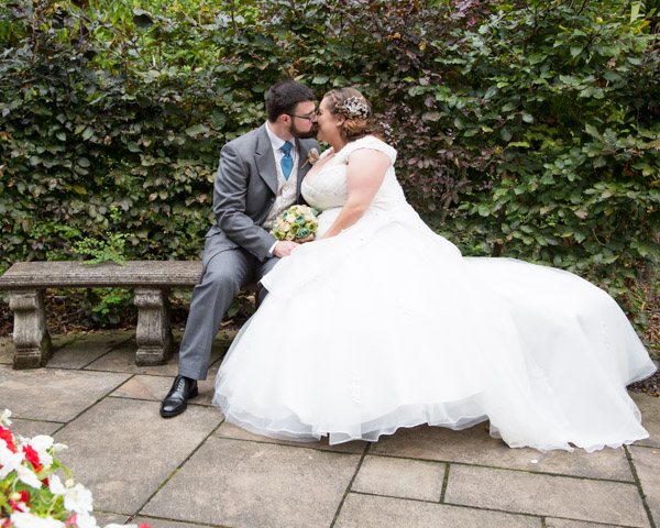 Bride and groom sitting on stone bench in front of green and red hedges at Chester Zoo wedding
