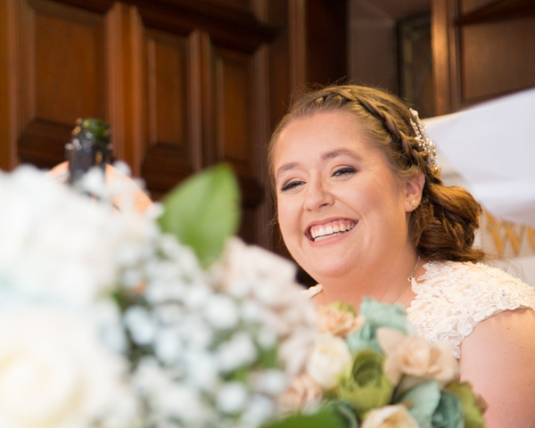Bride laughing at the top table during the wedding speeches