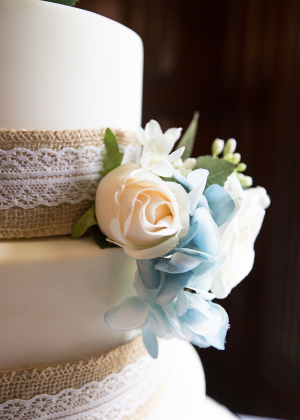 The side of the wedding cake with hessian ribbon and blue and peach roses