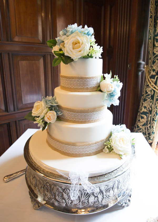 The wedding cake with hessian and lace ribbon standing on a silver cake stand