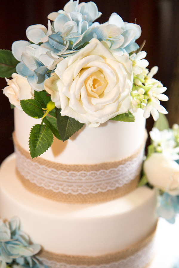 Blue white and peach flowers on the top of the wedding cake all hand made with icing
