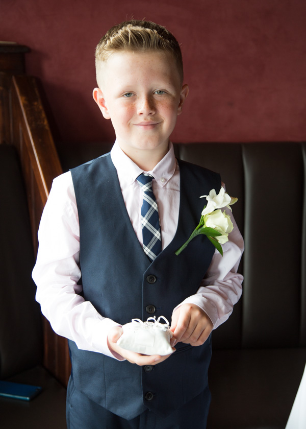 Young Groomsman with white rose corsage holding the wedding rings