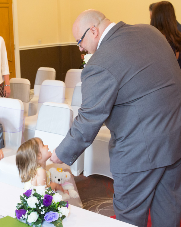 Groom talking to a toddler as the guests come into the ceremony room