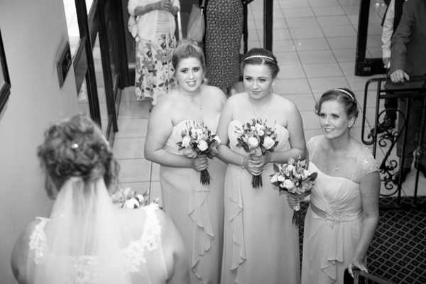 Bridesmaids waiting at the bottom of the stairs waiting for the bride to walk down