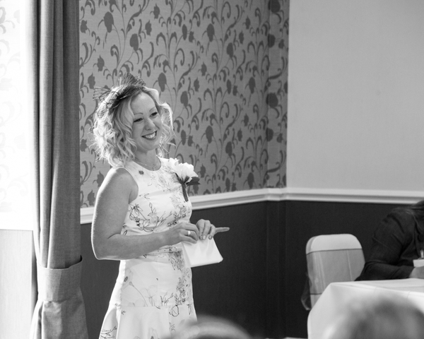 Wedding guest smiling at the front of the cermony room after doing a reading