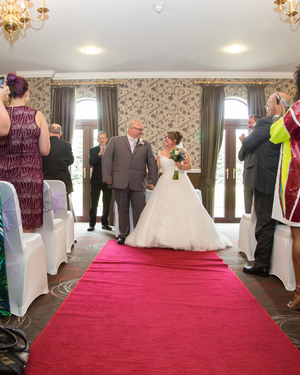 Bride and groom standing at the altar facing their guests at the end of a red carpet