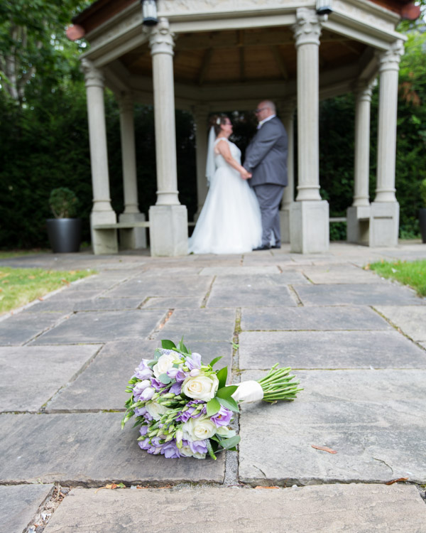 Bride and Groom looking at each other under the stone gazebo in the Secret Garden Holiday Inn Barnsley