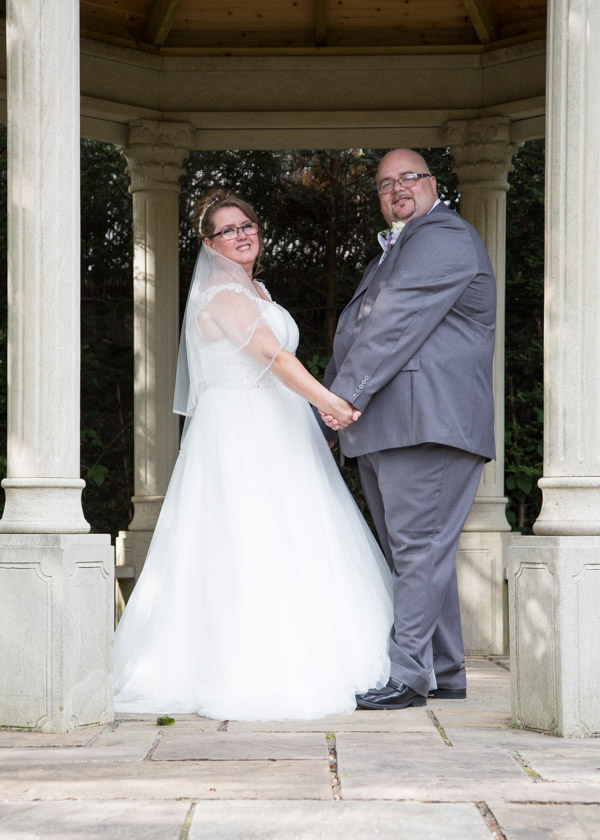 Bride and Groom looking at the camera from under the stone gazebo in the Secret Garden Holiday Inn Barnsley