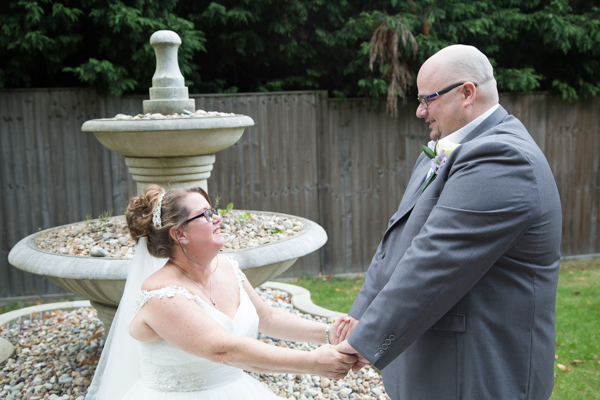 Bride and Groom sitting on the stone water fountain in the secret garden Holiday Inn Barnsley