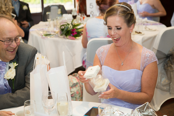 Bridesmaid in lilac dress opening her wedding gift at the table and laughing
