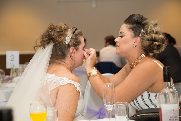 WEdding guest reapplying brides false eyelash at the wedding breakfast table