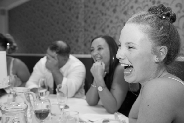 Wedding guests laughing around the wedding breakfast table