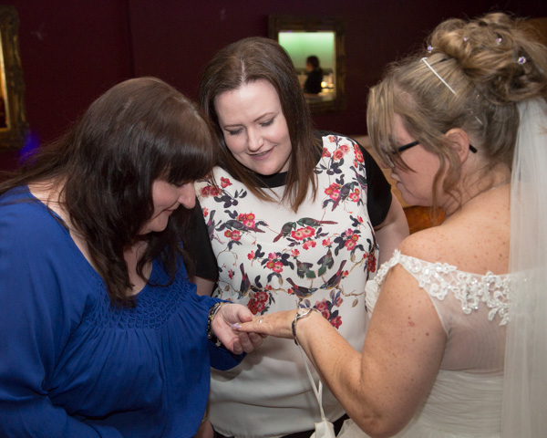 Wedding guests admiring brides ring in scarletts bar Holiday Inn Barnsley