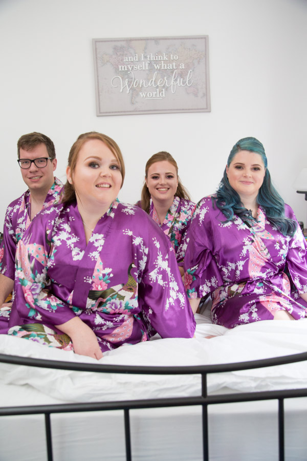 Bridesmaids in matching purple robes sitting on a white bed with sign in the background