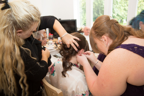 Bridesmaids and hairdresser helping the bride get ready before the wedding